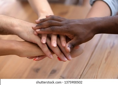 Close up different ethnicity women and men holding hands together multiracial people starting common business celebrating success at work or study, gesture and symbol of trust unity support friendship