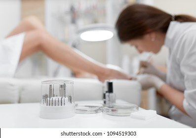 Close up of different professional cosmetics and oils, tools for french pedicure on white table. View from distance of specialist wearing gloves making pedicure for client in arm chair. Beauty salon.