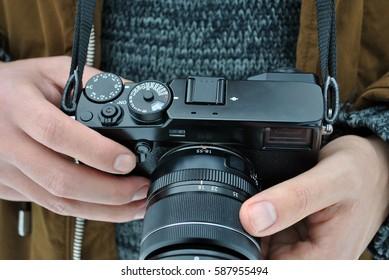 Close up of a digital photo camera in man hands.