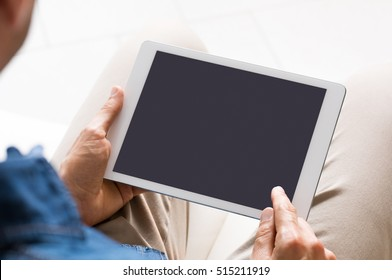 Close up of digital tablet screen while man working on it. Young businessman switching on tablet to start his work. Young man looking at a blank black screen of tablet.