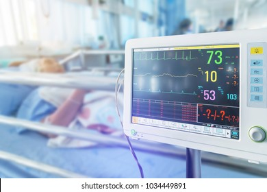 Close up  digital vital signs of  measuring heart and blood pressure monitor with elderly patient sleep on the bed in hospital ward room