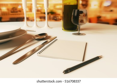 Close up of dining table with blank spiral notepad, candles, wine, cutlery and other items. Restaurant rating and criticism concept. 3D Rendering