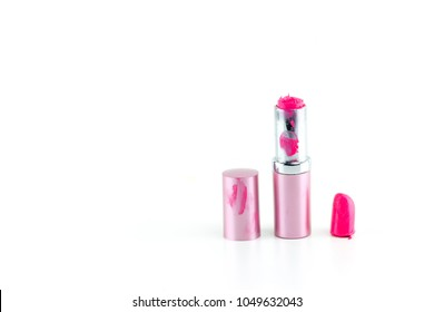 Close up dirty broken pink lipstick isolated on white background with copy space. woman make up concept.
