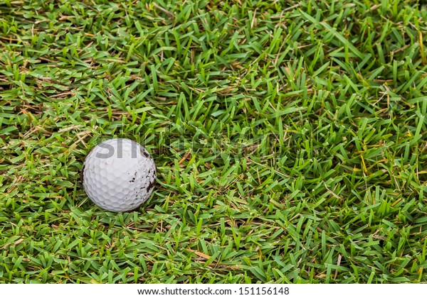 Close up dirty golf ball on the fairway