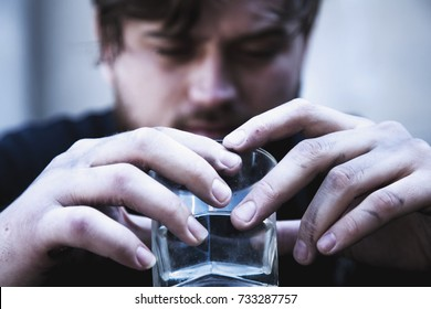 Close up of dirty man holding a glass of vodka. Drunk young people. (alcoholism, pain, pity, hopelessness, social problem of dependence concept)