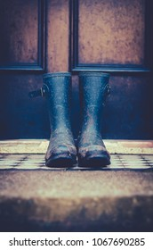 Close Up Of Dirty Rubber Boots Outside a Front Door