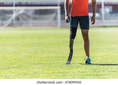 Close up disabled man athlete with leg prosthesis. Paralympic Sport Concept.