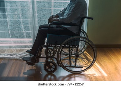 close up of Disabled Sad man handicapped sitting on wheelchair in front of window in hospital,He is sad and lonely.