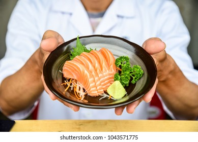 Close up dish of salmon sashimi with vegetable and fresh wasabi in chefs hands, raw fish in traditional Japanese style.