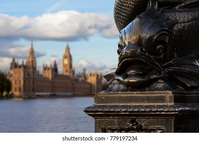 Close up of the distinctive fish design on the cast-iron lamp posts in Westminster, London with the Houses of Parliament out of focus in the background.