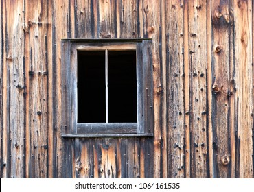Close up of Distressed Barn Wall with Window has Light and Dark Boards with Discoloration and Nails.