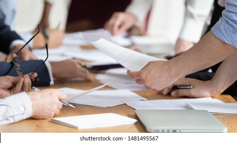 Close up of diverse businesspeople brainstorm discussing paperwork share project ideas together, employees gather consider financial paper handout material, company statistics at office briefing
