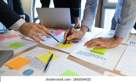 Close up of diverse businesspeople working on project startup presentation in team, comparing statistic data, studying values on graph diagrams, analyzing trends patterns, making notes on paper sheets