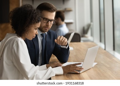 Close up diverse colleagues working on online project together, discussing financial statistics, using laptop, Caucasian businessman mentor training African American young businesswoman intern