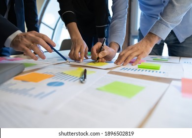 Close up diverse employees working on financial project statistics or report, writing notes on colorful sticky papers, checking documents, coworkers developing business strategy, teamwork