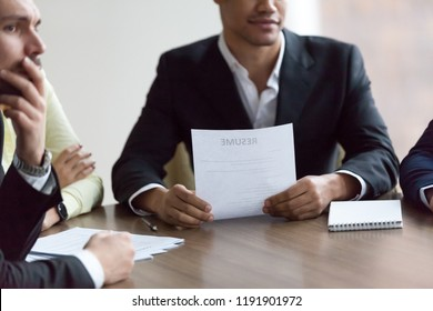 Close up of diverse HR managers consider job applicant during work interview in office, thoughtful recruiters think about candidate, reading resume, listening to qualifications. Hiring concept