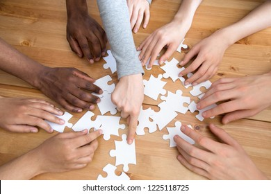 Close up diverse multiracial people hands assembling puzzle scattered on wooden table, top above view. Symbol and metaphor of teamwork and connection, business strategy and logic thinking concept