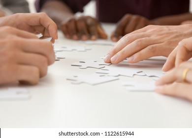Close up of diverse people hands assembling jigsaw puzzle together, multiethnic work team looking for business solution, showing unity, helping each other and cooperating. Teambuilding concept