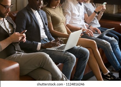 Close up of diverse young people being addicted to gadgets, sitting in queue using phones and laptops, multiracial millennials busy chatting or checking email on smartphones, obsessed with technology