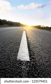 Close up of dividing line on asphalt road at sunset