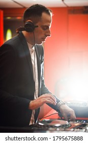 Close up of DJ with headphones at night club party. Man in black suit playing music on deck with vinyl record in red black interior