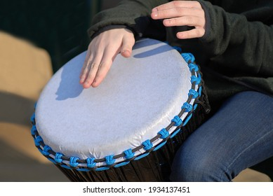 Close up djembe, ethnic percussion instrument. Street musician plays drum with their hands. No face. Oudoors. Sunny day.