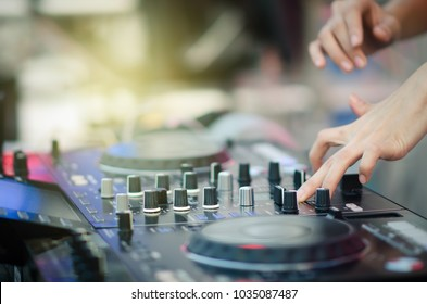 Close up of DJ's hand playing music at turntable on a party festival, Turntable vinyl record player,analog audio equipment for disc jockey to scratch vinyl records.