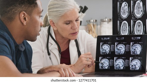 Close up of doctor consulting with patient on his concussion looking at ct scans