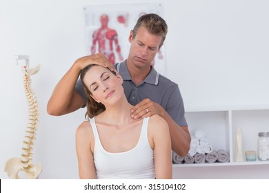 Close up of doctor doing neck adjustment in medical office