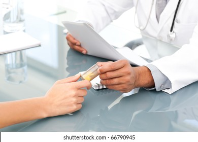 Close up of a doctor giving drugs to his patient during an appointment in his office