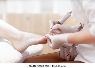 Close up of doctor in gloves making procedure for foot with special electric equipment fo client. Caring about foot and nails at beauty salon. Podiatry and medical concept.