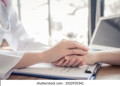 Close up of doctor hand reassuring her female patient at hospital. Closeup hands of medical doctor carefully holding patient's hands. Kind doctor giving real support for patient, soft focus.