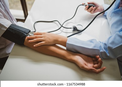 Close up of doctor hands checking blood pressure of a patient.Medical care concept.