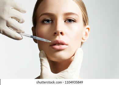 Close up of doctor hands with syringe and female beautiful face. The young charming woman having procedure of enlarging lips. Beauty and treatment concept. Isolated on grey background