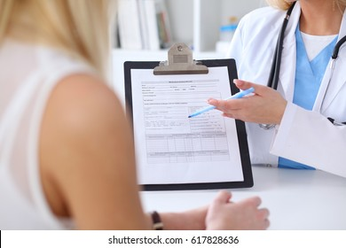 Close up of a doctor and  patient hands while physician pointing into medical history form at clipboard. Medicine and health care concept