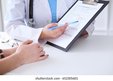 Close up of a doctor and  patient hands while phisician pointing into medical history form at clipboard