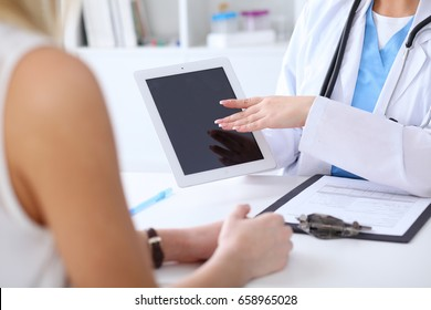 Close up of a doctor and  patient hands while phisician pointing into tablet computer monitor