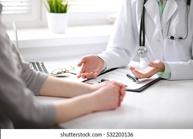 Close up of doctor and  patient  sitting at the desk near the window in hospital