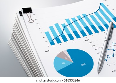 Close up of documents and charts. Pile of documents and pen on gray reflection background.