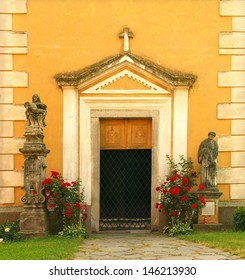 Close door into traditional church from sixteenth century, red rouses and two sculptures of saints at the door.