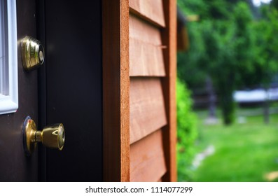 Close up of a door knob and dead bolt with cedar house siding and a lawn in the background