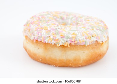 Close up of a doughnut with multi coloured icing sugar against a white background