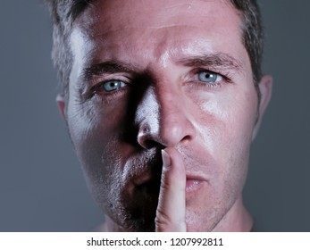 close up dramatic studio portrait of young handsome and attractive man with finger on his closed mouth warning to shut up and not to speak in censorship and freedom of speech coercion