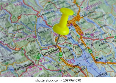 Close up of Drammen, a city in Norway, pinned on a map with yellow pin. Travel concept. Selective focus.