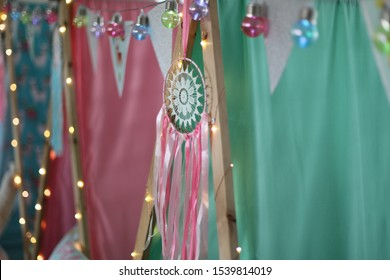 A close up of a dream catcher on teepees at a girls sleepover party.