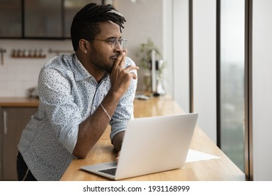 Close up dreamy African American man wearing glasses looking to aside out panoramic window, visualizing, pondering new opportunities or online project strategy, standing at table with laptop