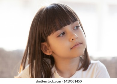Close up of dreamy little girl look in distance thinking of something, thoughtful cute preschooler kid distracted dreaming or visualizing, small child lost in thoughts, planning or imagining