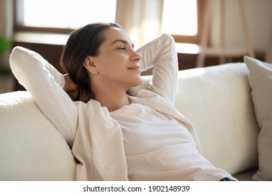 Close up dreamy smiling woman daydreaming, stretching on sofa with hands behind head, happy young female visualizing good future, enjoying lazy weekend, sitting on comfortable couch at home