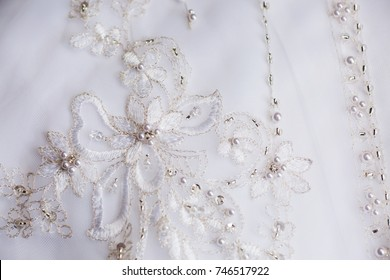 Close up dress detail of delicate lace embroidery on a white wedding gown