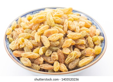 Close up of dried vine fruit of golden raisins or sultanas in porcelain bowl isolated on white background,studio shot